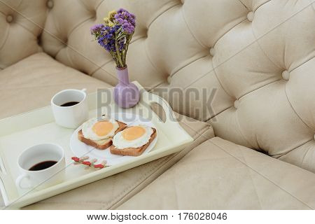 Close up of toasts with fried eggs, cups of coffee and flowers on tray on sofa