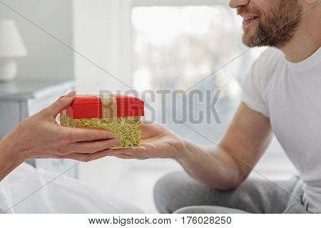 Happy man is giving present to woman. He is sitting on bedding and laughing. Focus on colorful box