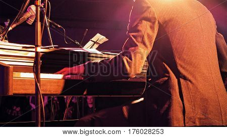 Piano player plays the piano keyboard on the stage with sound lights. Jazz retro vintage concert performance entertainment. Close up shot with selective focus.