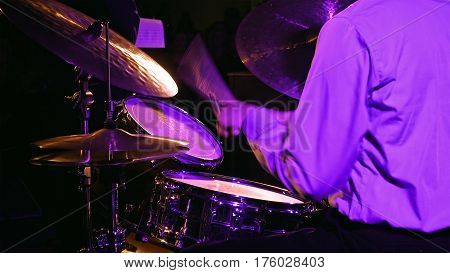 Drummer plays on drum set and cymbal with drumsticks on the stage. Jazz or rock concert performance entertainment. Close up shot with soft selective focus.