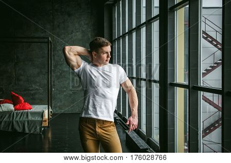 Young Sexy Men Bodybuilder Athlete, Studio Portrait In Loft On The Background Of Stylized Wall And B
