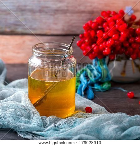 Jar of honey and the branches of viburnum on the table. Honey and viburnum on blue napkin . Wooden background. The concept of healthy food. Selective focus