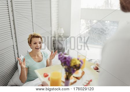 Man is caring about his wife. He is bringing healthy breakfast to bed. Happy woman is smiling with excitement