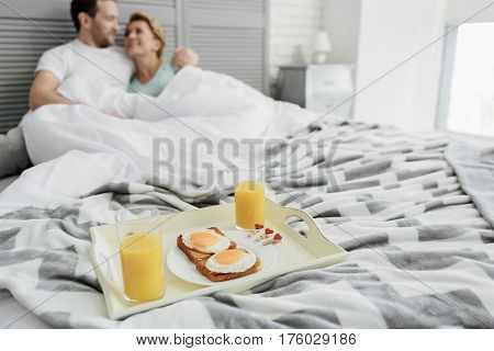 Romance is still alive. Happy married couple is sitting in bed and hugging with love. Focus on tray with fried egg toasts and juice