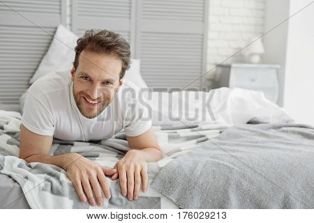 Portrait of happy man is lying and relaxing on bed. He is looking at camera and laughing