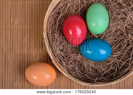 Three multicolored eggs in the straw in a basket and one egg on a mat next