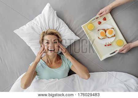 Top view of excited woman lying on bed near tray with romantic breakfast in male arms. She is looking at camera and laughing