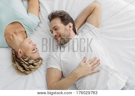 You are my only one. Joyful middle-aged man is looking at woman with love. They are lying on bed and smiling. Top view