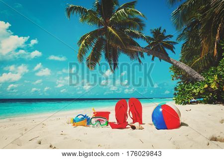 slippers, toys and diving mask at beach- beach vacation concept