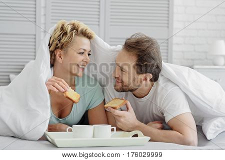 Cheerful married couple is eating toasts with coffee and talking. They are lying on bed under quilt and smiling