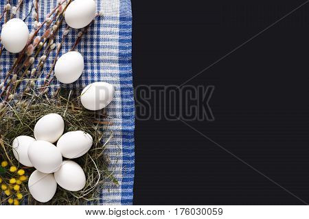 Easter mockup. White eggs unpainted in hay nest, pattern for your colors, on napkin at black background decorated with mimosa and pussy willow spring flowers. Top view with copy space