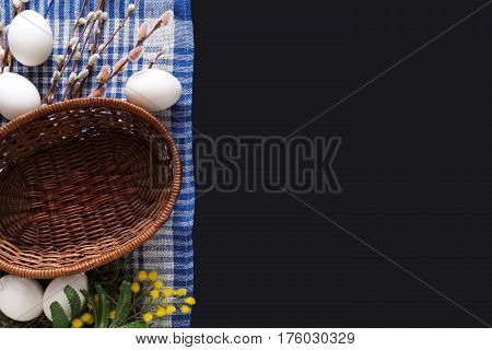 Easter mockup. White eggs unpainted, pattern for your colors, and empty basket on napkin at black background decorated with mimosa and pussy willow spring flowers. Top view with copy space
