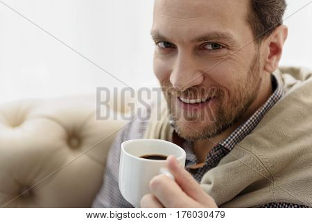 Portrait of happy man drinking coffee with enjoyment. He is looking at camera and smiling. Copy space in left side