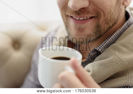 Close up of joyful guy enjoying coffee and smiling. He is holding white cup