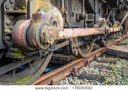 Closeup of the weathered drive mechanism of an old diesel-electric locomotive parked on rusty rails in the Netherlands.