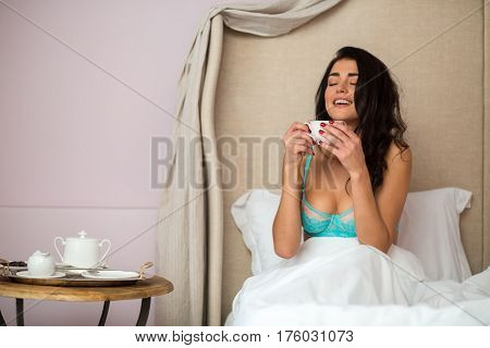 Lady with cup in bed. Woman with closed eyes smiling. Coffee early in the morning.