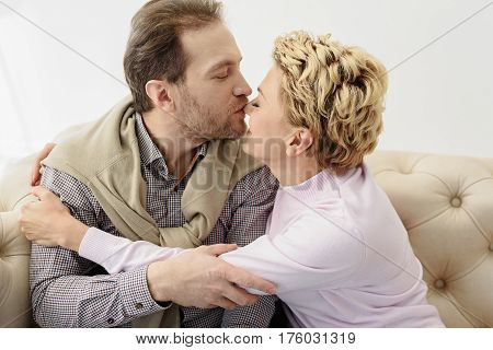 Happy married couple is kissing with love. They are sitting on sofa and hugging