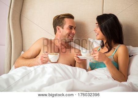Couple with coffee in bed. Man holding cup and smiling. Morning chit chat.
