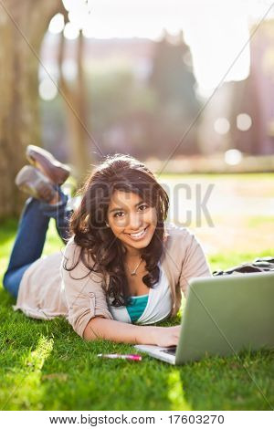 A shot of an asian student using laptop on campus