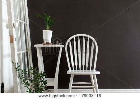 The interior is furnished with a white chair, a table with flowers opposite the black wall.