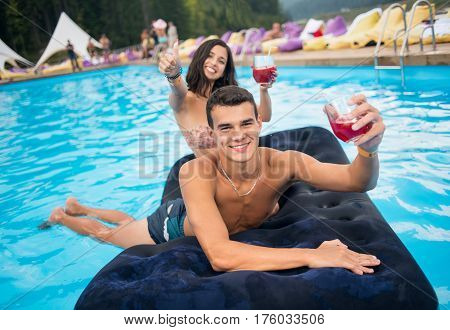 Young Smiling Man With Cocktails Lying On An Inflatable Mattress In Pool With Woman Out Of Focus Nex