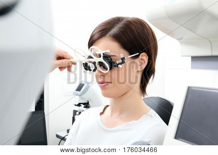 optician with trial frame optometrist doctor examines eyesight of woman patient