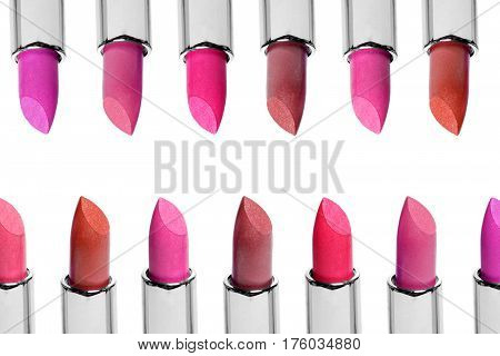 Set of color lipsticks arranged in line isolated on white background. A rows of red, pink and wine lipstick.