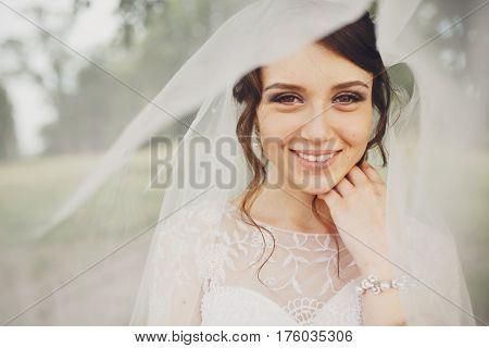 Brunette Bride With Hazel Eyes Smiles Under A Veil