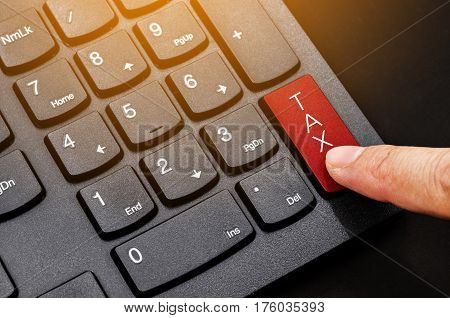 Taxes concept. Number button on computer keyboard with tax button and finger.