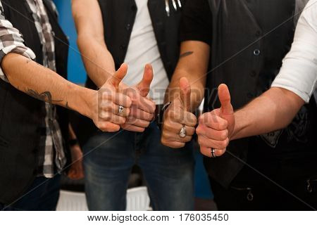 Welcome to our professional team. Close-up shot of young barbers posing to camera with thumb up gesture, inside modern barbershop. Four masculine male hairstylists at work place in hair salon