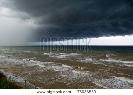 Storm front over water with wall of rain in the centre