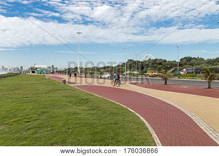 People Walking On Paved Promenade On Beachfront