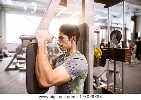 Young hispanic fitness man in gym sitting on bench, working out with weights. working on fitness machine at the gym. butterfly machine with weights in a gym