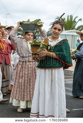 FUNCHAL MADEIRA PORTUGAL - SEPTEMBER 4 2016: Girls carry the baskets of grapes in traditional costume durnig historical and ethnographic parade of Madeira Wine Festival in Funchal. Madeira Portugal