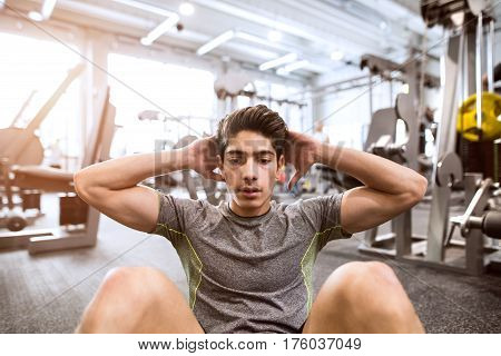 Fit hispanic man at abdominal crunch muscles exercises during training in fitness gym