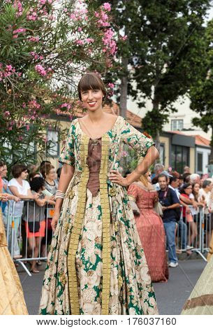 FUNCHAL MADEIRA PORTUGAL - SEPTEMBER 4 2016: Woman in historical fashion dress durnig historical and ethnographic parade of Madeira Wine Festival in Funchal. Madeira Portugal