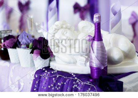 A Porcelain Angel Lie On A Violet Cloth Behind A Champagne Bottle Enveloped In Violet Ribbons. Resta