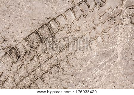 Tire tracks on a wet muddy road abstract background
