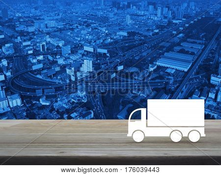 Truck flat icon on wooden table over modern city tower street and expressway Business transportation service concept