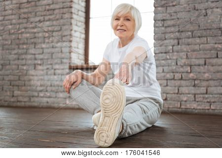 Keep fit. Positive delighted woman wearing white T-shirt and grey trousers looking on camera while stretching her body