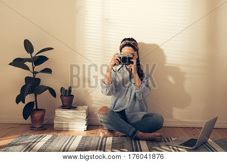 Young Woman Taking A Photograph At Home