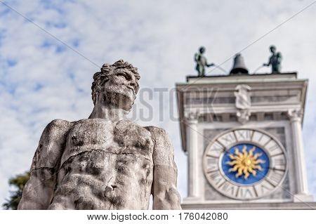 Statue of the 16 century. Statue of Hercules. Medieval art.Blurred in background the clock tower