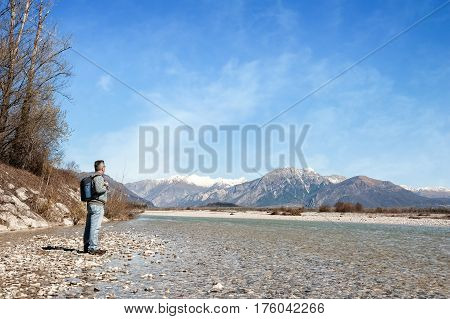Mature Hiker On The Bank Of A River. Walking Toward Mountain.