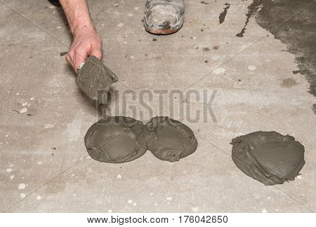 Worker Put Adhesive On Floor With Trowel