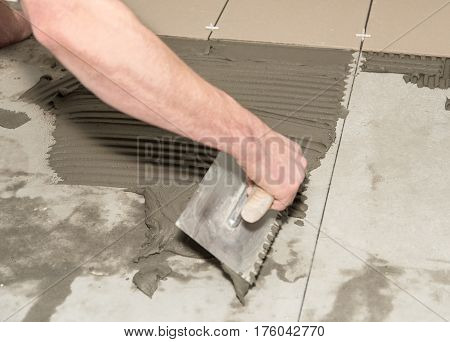 Home Improvement, Renovation. Construction Worker Is Tiling, Ceramic Tile.