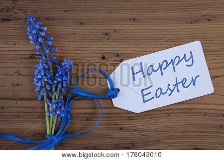 Label With English Text Happy Easter. Blue Spring Grape Hyacinth With Ribbon. Aged, Rustic Wodden Background. Greeting Card For Spring Season