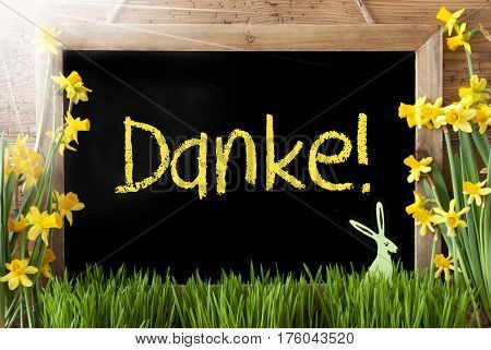 Blackboard With German Text Danke Means Thank You. Sunny Spring Flowers Nacissus Or Daffodil With Grass And Easter Bunny. Rustic Aged Wooden Background.