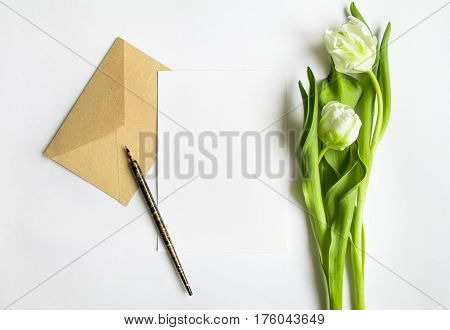 Letter envelope and couple of fresh tulips on white background. Wedding invitation card or love letter with white flowers. Romantic or holiday concept top view flat lay overhead view
