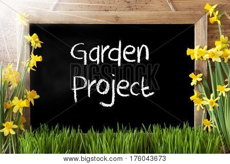Blackboard With English Text Garden Project. Sunny Spring Flowers Nacissus Or Daffodil With Grass. Rustic Aged Wooden Background.