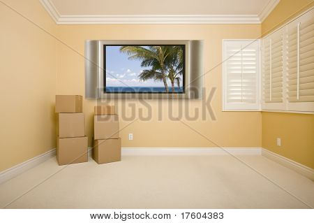 Flat Panel Television on Wall with Tropical Scene in Empty Room with Boxes.